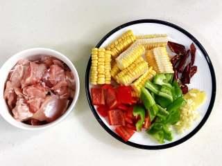 香菇炖鸡,把鸡腿剁块,玉米、青椒、红椒、干辣椒和姜蒜切好。