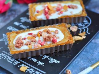 奶酪蜜薯麦片派,取出后晾凉,表面倒些酸奶,再撒些草莓酸奶燕麦片。