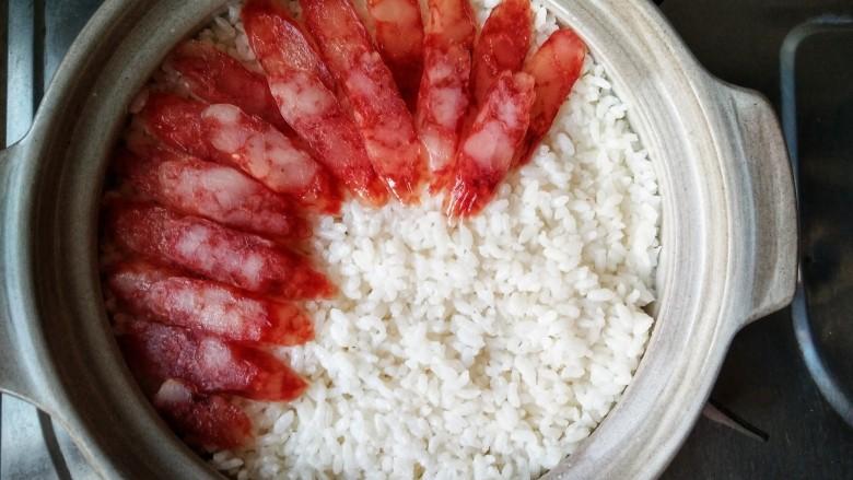 腊味煲仔饭,再将腊味铺在米上,因为这样腊肠的咸度会更低一些,然后再煮5分钟,在煲煮的过程中,米饭会自动吸收腊味的精华,米饭被肉香包裹,才是煲仔饭的正道。