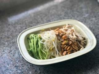 麻辣拌面,捞出面条,把黄瓜丝、绿豆芽、花生米和鸡丝码在面上。