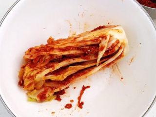 韩式辣白菜,取一块腌好的白菜,在每个叶片里面抹上一层厚厚的辣酱