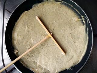 杂粮煎饼,用煎饼推子围中心打圈绕圆,把面糊在锅中推开摊平,中小火加热。(薄厚根据个人喜好)