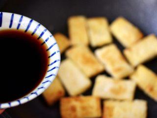 照烧北豆腐,这个时候锅中倒入调制好的调料汁,把煎好的豆腐都均匀地沾上调料汁。