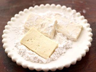 照烧北豆腐,盘子里放入适量的淀粉,把切片豆腐裹上一层薄薄的淀粉。