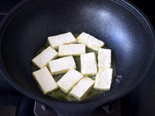 照烧北豆腐,锅烧热后倒入花生油烧热,放入裹好淀粉的豆腐。