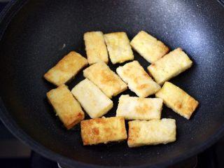 照烧北豆腐,看见一面煎至金黄色后,再把另一面也煎制金黄色的时候。