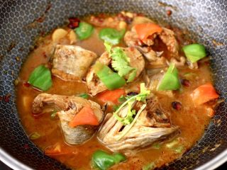啤酒焖鳕鱼,大火继续烧至青红辣椒断生变色的时候,撒上香菜段即可关火。
