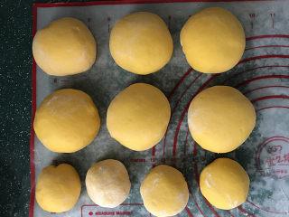 南瓜豆沙馒头,将其中的6份面团,依次放案板上揉一揉,揉成团;余下的2份,每个对半切开成4小份,盖上保鲜膜松弛15分钟左右
