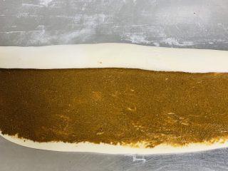 芝麻烧饼,均匀的涂抹上芝麻酱,从上向下卷起。
