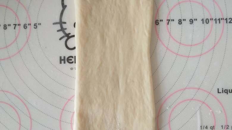 酸奶土司,8、取一个面团擀开,翻面,压薄底边、