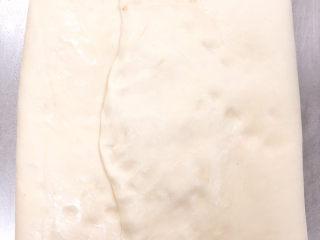醇香巧克力吐司,将面团的两边折叠,把馅料包裹在面团里,边边的位置用面团捏紧,拿擀面杖稍微擀一下,然后封保鲜膜放冰箱冷冻20min。