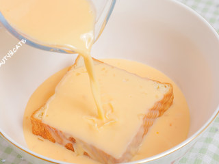 泡过牛奶浴的吐司,在我心中排名第一!!!,切好的吐司放进碗里,倒入蛋奶液,盖上保鲜膜,放入冰箱中冷藏一夜