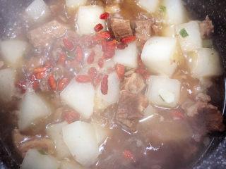 萝卜牛腩煲,炖煮10分钟,加入少量枸杞子。
