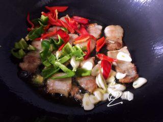 杏鲍菇炒肉片,肉片变色后,放入青红椒和蒜片翻炒均匀