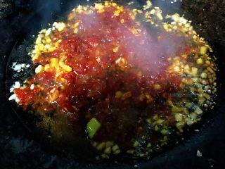 彩椒辣酱炒花螺,锅中放入底油加热放入蒜末爆香在放入自制蒜蓉辣椒酱炒匀