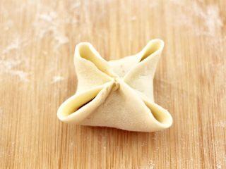 四喜饺子,把饺子皮的中间部分捏紧,如图。