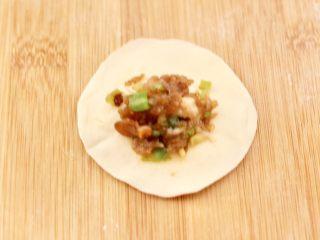 四喜饺子,取一个饺子皮,上面放入适量馅料。
