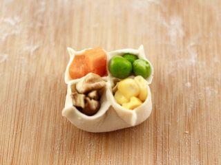 四喜饺子,把胡萝卜、玉米粒、青豆和香菇丁,依次放入点缀。