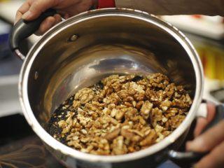 自制即食阿胶,将黑芝麻用平底锅炒熟备用。 将核桃仁清洗干净,掰碎,核桃仁块的大小随意,然后将核桃仁放在烤箱里烤熟,或者用微波炉烤熟,备用。