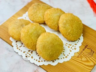 东北油炸糕,炸至两面金黄,炸糕漂浮在油面上就熟了,捞出放在吸油纸上吸去多余的油脂。
