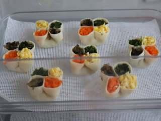 虾仁四喜饺子,分别往每个饺子的圆洞里填入胡萝卜碎,荠菜碎,木耳碎和鸡蛋碎,填的时候可以用一个小点的勺子装馅,比用筷子方便。