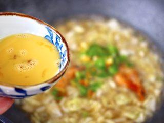 大白菜海虾打卤面,鸡蛋打散后,慢慢倒入锅中。