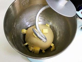 奶香面包,揉至成团,可以拉出粗膜,往搅拌桶内加入黄油。