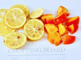 水果花茶,柠檬用刀切成薄片,柿子洗净后用刀切小块。