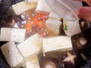 海鲜豆腐煲,煮开锅后,放入一个骨汤浓汤宝。盖盖儿小火儿炖煮5分钟。