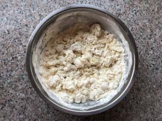 四喜蒸饺,慢慢将温水倒入面盆,把面粉搅成絮状。