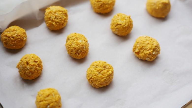 南瓜燕麦饼,取适量南瓜泥,搓成小球,放在铺了烘焙纸的烤盘上。