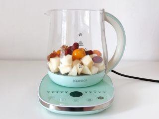 冰糖雪梨金桔饮,往康佳养生壶内加入雪梨、金桔、红枣和冰糖。