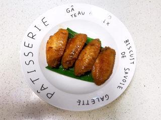 可乐鸡趐,先把香蒜叶放入盘底,再把烧好的可乐鸡翅夹出来
