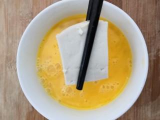 鱼香脆皮豆腐,把切块的豆腐,放入鸡蛋液中,让鸡蛋液,粘满豆腐