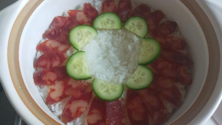 广式煲仔饭,摆放一圈腊肠,在摆黄瓜片,中间用勺子压一个坑。