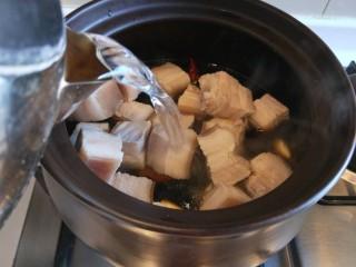家常卤肉饭,倒入酱油,料酒,老抽,倒入一壶开水。