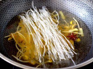 苔菜海虾粉条一锅炖,看见黄豆芽翻炒至变软后,锅中倒入适量的清水,先放入洗净的地瓜粉条。