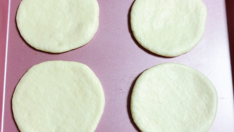 蓝莓芝士迷你披萨,将面团擀成圆形,披萨胚就做好了,放入烤盘中。提前预热烤箱180度预热10分钟。