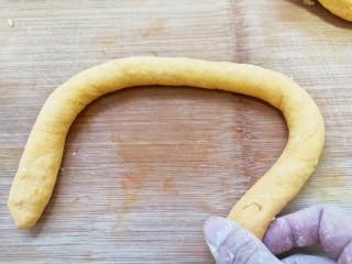 奶香南瓜麻花,把面團分成幾個相同的小劑子,小劑子揉成長條。
