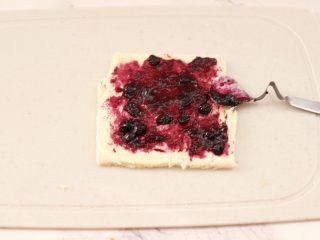 快手早餐-香蕉蓝莓吐司卷,在擀薄的吐司片上,均匀地抹上有颗粒的蓝莓酱。