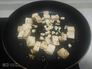 内酯豆腐炒平菇、鱼块,锅中放入适量油,放入豆腐煎至一面金黄,放入蒜瓣