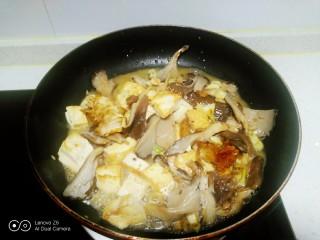 内酯豆腐炒平菇、鱼块,加入盐,翻炒均匀