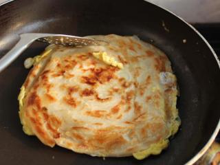 香酥的手抓餅,一面煎好,翻面。兩面金黃,用鏟子輕輕從餅邊向內擠壓,把餅打松散。