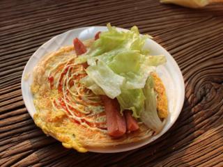 香酥的手抓餅,有雞蛋那一面擠上沙拉醬,番茄醬。擺上香腸,洗凈擦干的生菜。
