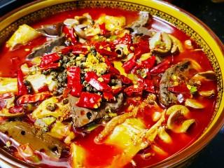 毛血旺,将汤汁通过漏勺倒入碗中,上面铺上花椒和干辣椒