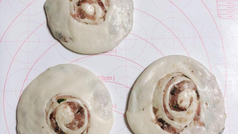 梅干菜烧饼,切面朝上立在案板上,用手掌压扁。压成小圆饼状。