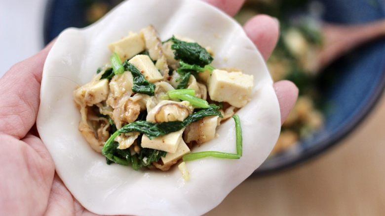 萝卜樱海鲜豆腐蒸饺,饺子皮上放入适量的馅料。