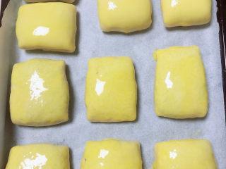冬至美食 新疆烤包子,在烤包子上刷上一层蛋黄液。将烤盘放入烤箱中,180度烤20分钟,18分钟的时候看一下烤箱,避免上层皮烤糊。