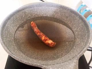 冬至美食   快手菜腊肠炒萝卜,四川腊肠提前放入锅中煮20分钟,煮熟后捞出来备用