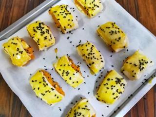 奶香红薯饼,摆在烤盘中,刷蛋液,撒上黑芝麻。
